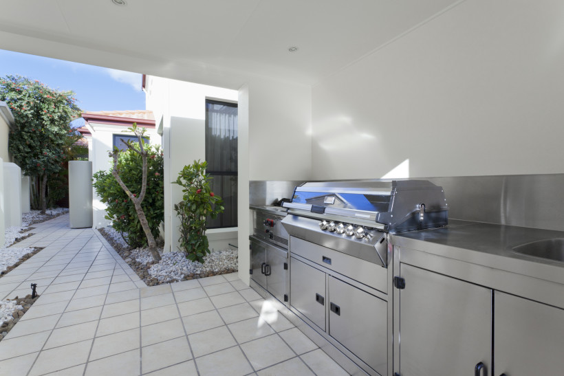 Outdoor covered stainless steel barbeque kitchen area at the rear of a modern home