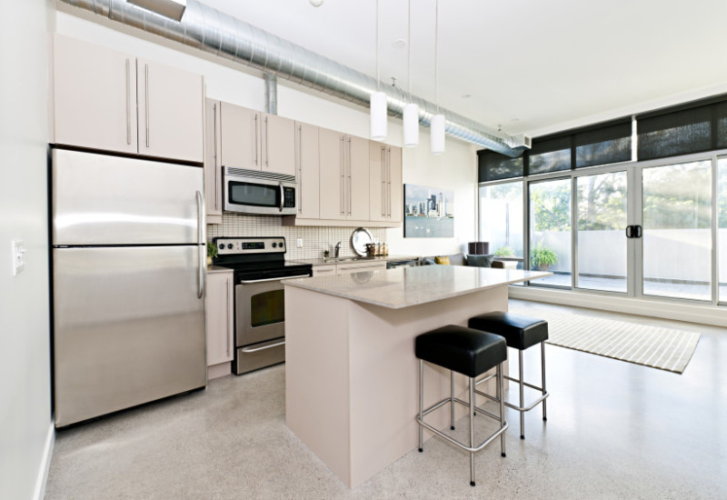 Modern condo kitchen and living room with simple island, two chairs and a polished concrete floor in a loft apartment