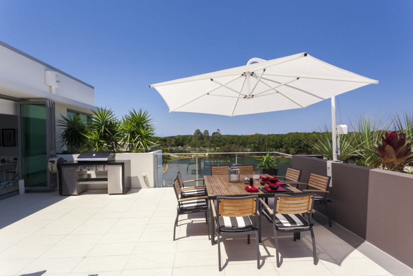 Outdoor balcony entertaining area with sunshade umbrella over table and chairs and quality barbecue