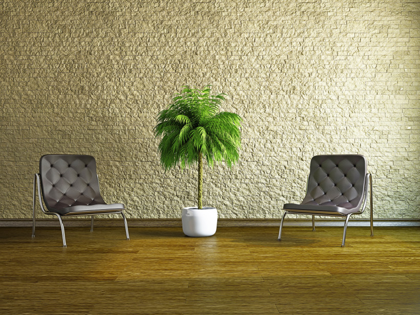 Sensational tan colored rough brick wall in a room with armchairs and potted palm plant