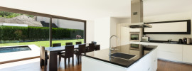 Modern villa interior with beautiful white kitchen, long island with tap and sink, dining table and timber floor
