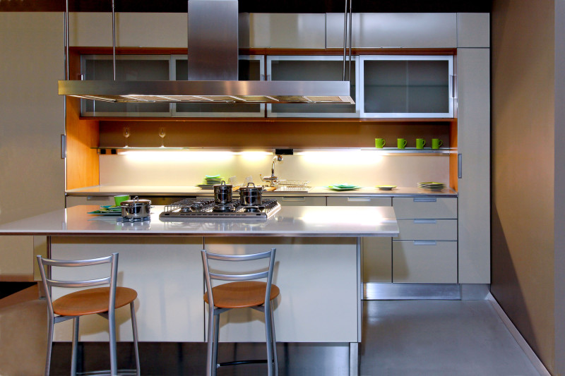 Modern simple kitchen with small central cooking island, bench space, overhead vent and night mood spot lighting