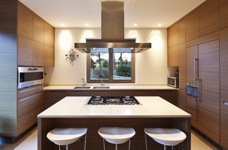 Beautiful apartment kitchen with functional island used for dining and cooking. The stunning wood panelled cabinets and the cream stone bench tops complement each other stylishly