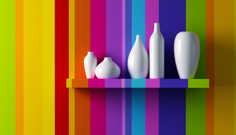 White vases contrasted against the effect of a multi colored shelf and wall