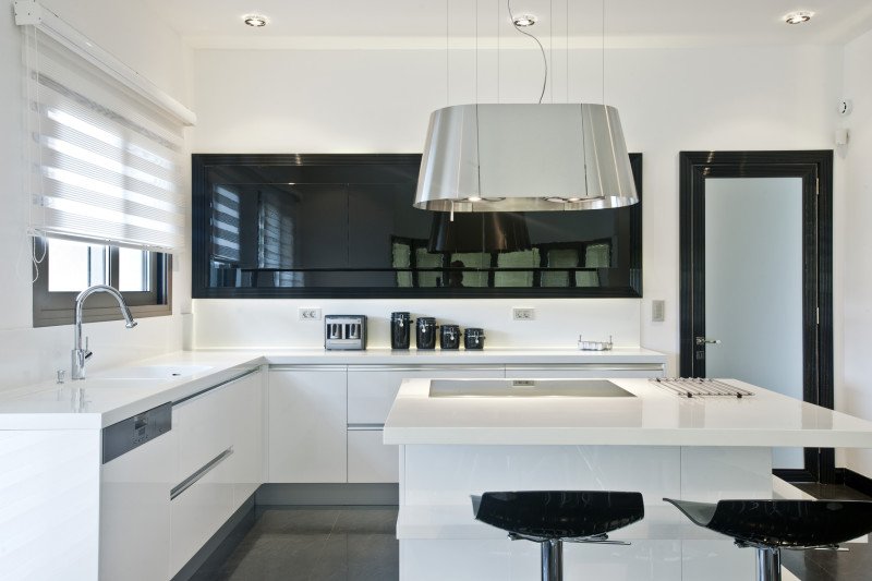 A modern brightly lit large kitchen with big white island which includes the cooker and seating places for dining