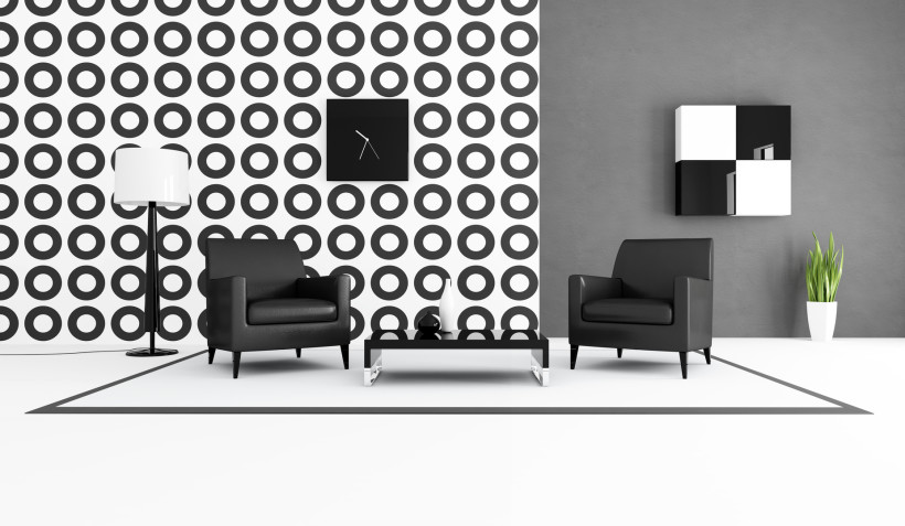 Contemporary black and white living room with two leather armchair in front a geometrical wallpaper and grey painted wall with black and white art piece