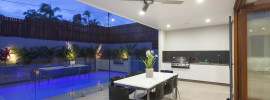 Modern backyard with glass panel fenced swimming pool and bbq cooking and dining area under cover off the main living room