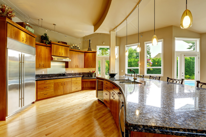 Spacious luxury kitchen room with extra large rounded kitchen island, black granite tops, honey colored wooden flooring and beautiful wooden cabinets