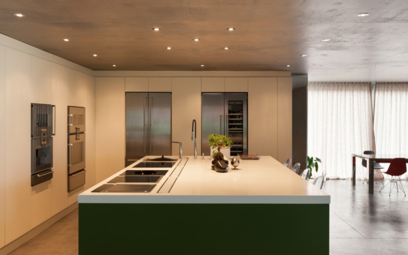 Modern home kitchen interior design with concrete ceiling and floor and large island bench area