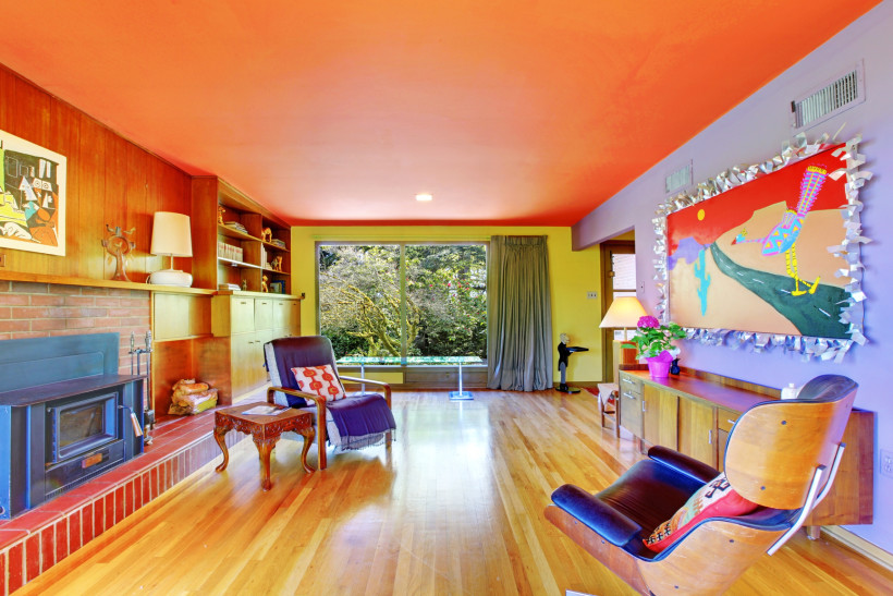 Bright and colorful retro modern living room with purple and yellow painted walls and orange ceiling