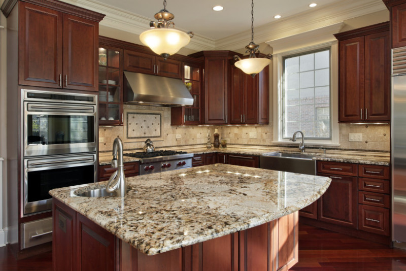 Kitchen with granite island and built in sink and tap, stainless steel appliances and rich cherry wood cabinetry