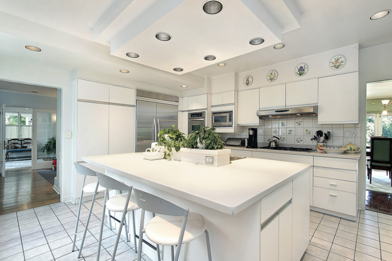 Beautiful modern kitchen with an abundance of white cabinetry, island bench with sink, stainless steel appliance and a concealed fridge