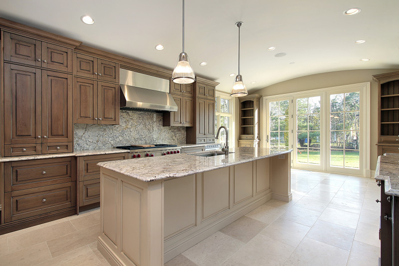 Large expansive kitchen with timber cupboards and a large marble topped island and floor