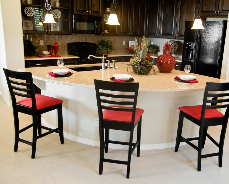 Beautiful large modern kitchen area with unusual shaped island and chairs designed for both dining and bench space