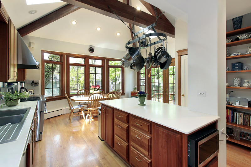 Kitchen with timber central island, stone bench tops, overhead pot storage and wood beams
