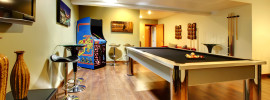 Fun play room home interior in the basement room of a luxury home with pool table, TV, games and no windows