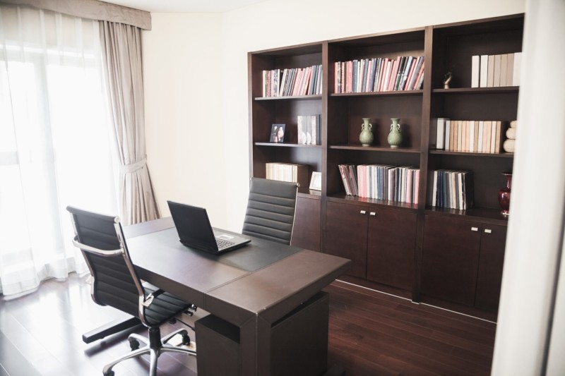 modern home office with large dark timber bookcase dark timber floors and desk and two