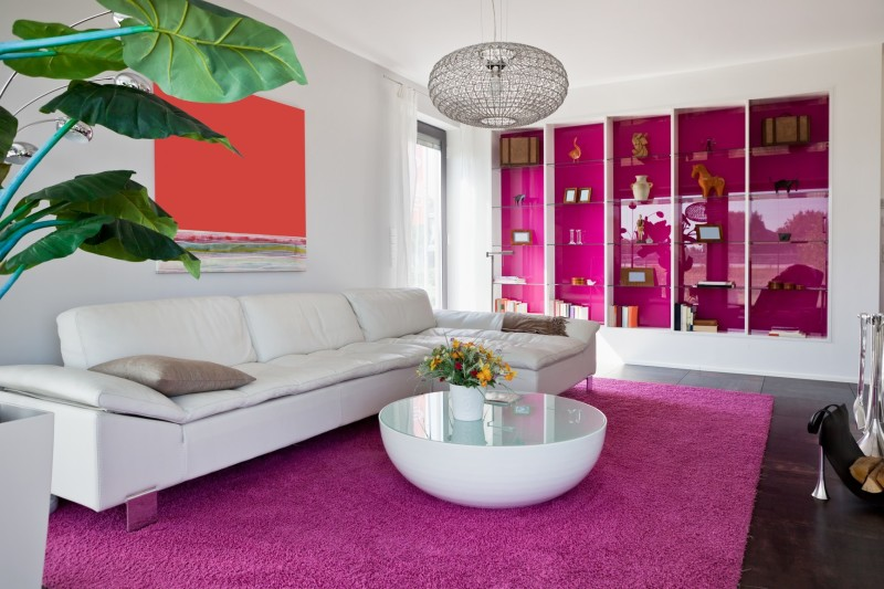 White Living Room And Furniture With Vivid Purple Display Cabinet And Carpet Rug Against A Dark