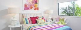 Girl's bedroom in modern townhouse with painted white walls, offset by colorful painting, bedspread and pillows