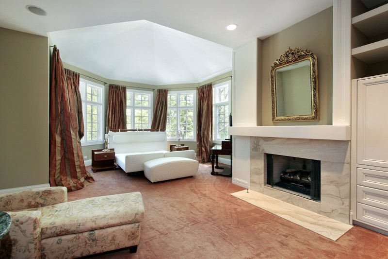 Beautiful Master Bedroom With White Bed Relaxing Chaise Stunning Rich Curtains And Marble Fireplace