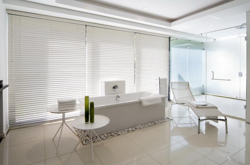 Stunning designer bathroom and shower with white rectangular bath tub set on a pebble base