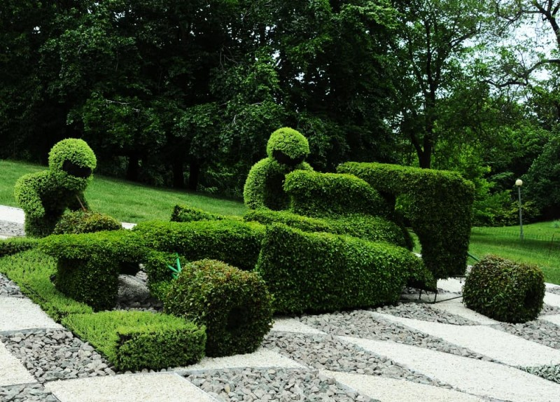 Abstract topiary art sculpted figures of motorcycle riders in the park