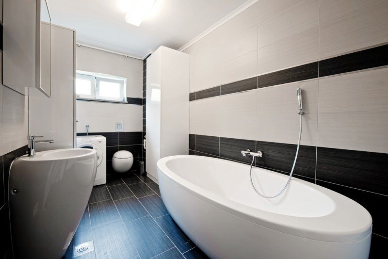 Modern bathroom with contrasting black wall and floor tiles against white bath tub, toilet and hand basin