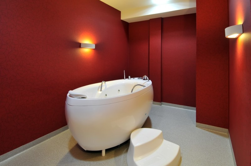 Modern red bathroom with specialized free standing hydro massage bath tub