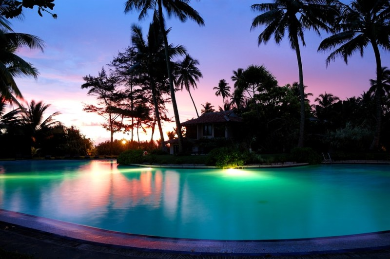 Sunset and illuminated massive swimming pool at Asian resort