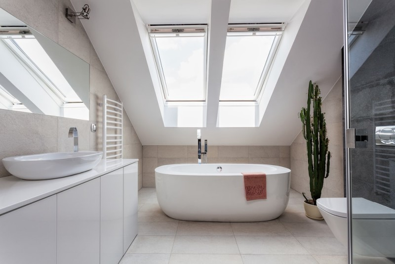 Urban apartment in the attic with sophisticated modern white bath tub and bathroom