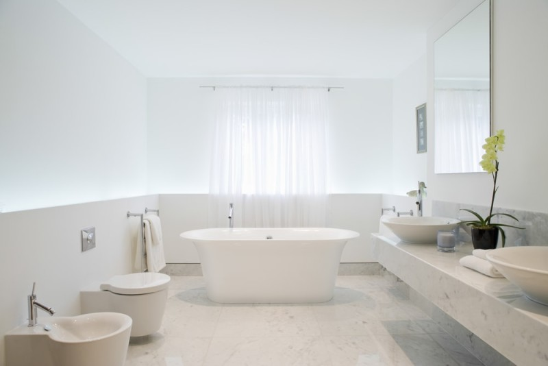 View of a spacious and elegant bathroom with modern white bath tub, marble floor and vanity bench