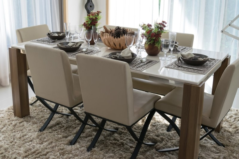 Gorgeous Marble Topped Dining Table With Six Place Settings, Comfortable  Soft Upholstered Chairs And Small Floral Arrangements In A Modern Home