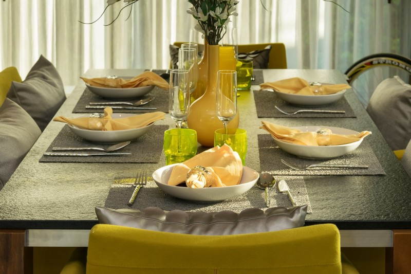 Lovely Dining Table With Six Place Settings Comfortable Yellow Chairs Matching Yelow Vases Floral Arrangement In A Modern Home
