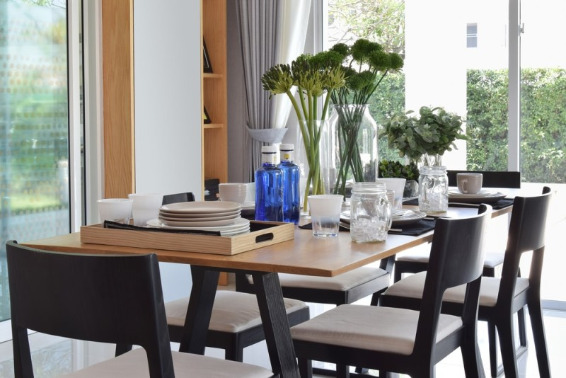 beautiful wooden dining table with modern comfortable chairs in a modern home with elegant table settings