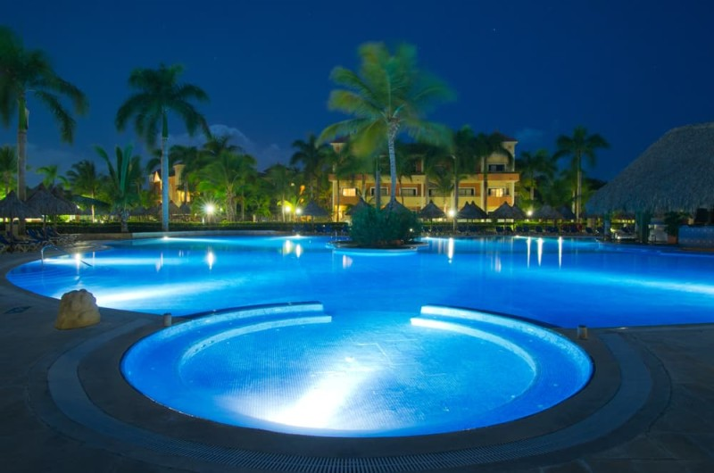 Heavily illuminated massive swimming pool in the evening in a tropical  location