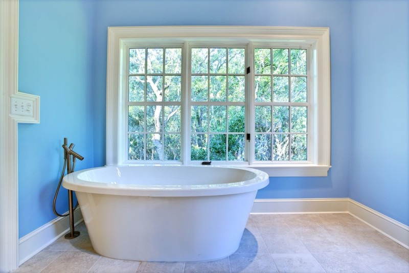 Ultra modern baby blue colored bathroom with modern oval shaped bath tub and window outlook