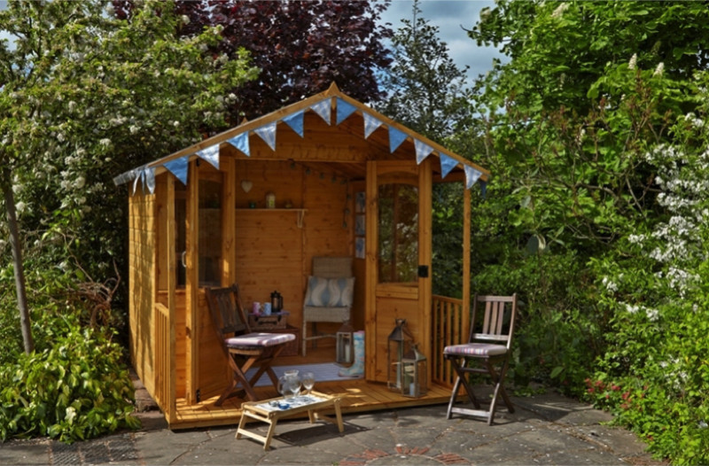 Small decorated wooden garden room with chairs and surrounded by bush