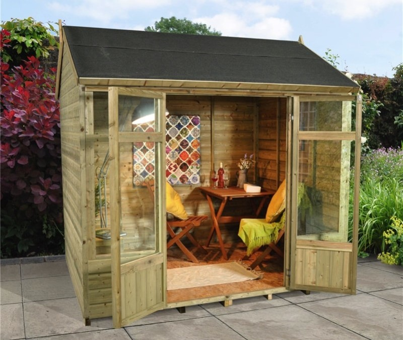 Compact wooden decorated garden room building with table and chairs