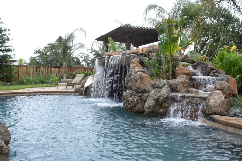 A waterfall into a swimming pool in a tropical landscaped backyard