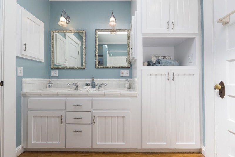Amazing white remodeled bathroom with fitted counters wooden floor and nicely decorated shelf min e1437858071898 - Blue and White Interiors