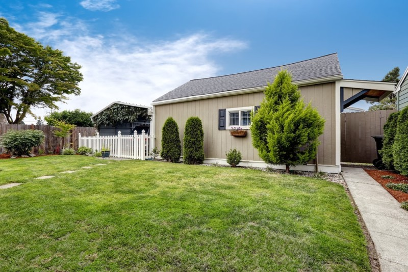 Backyard area with large garden room, picket fence and covered parking spot