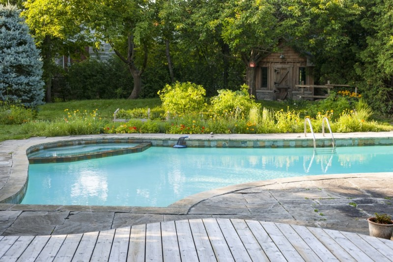 Backyard inground swimming pool with landscaped garden, gazebo, deck and stone patio
