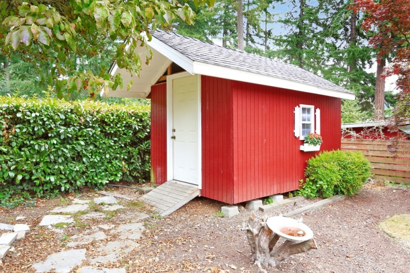 Bright red wooden garden room in a backyard area