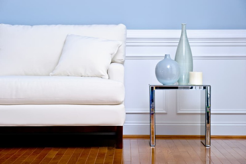 Cropped view of white couch and side table with vases in a living room with a wood floor min e1437892604206 - Blue and White Interiors