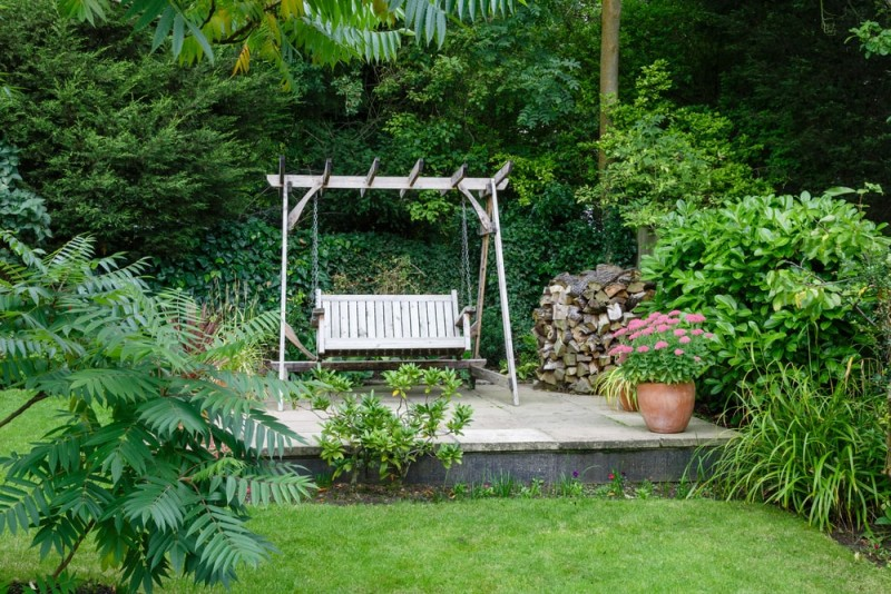 Mature garden landscape setting with small patio and timber swing seat