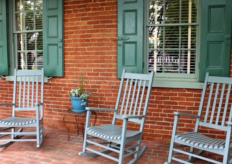 Inviting Front Porch With Brick Wall And Floor, Warm Green Shutters And A  Trio Of