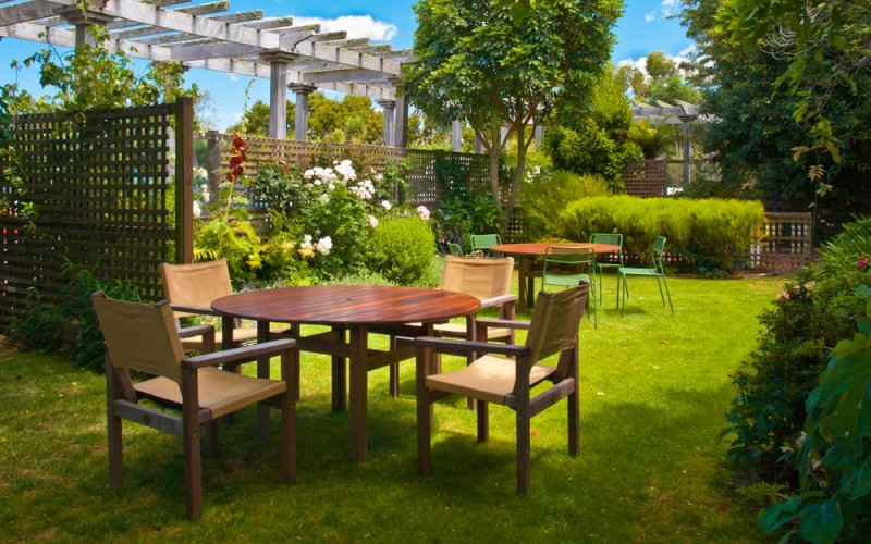Landscaped garden with two dining table sets, pergola, and trellis walls
