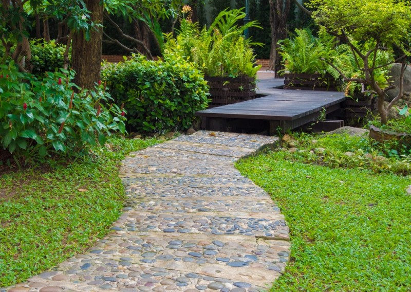 A beautiful landscaped pebbled pathway and boardwalk in the garden