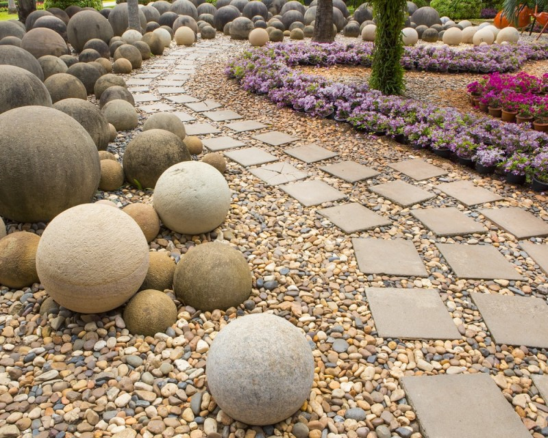Interesting landscaping in the garden with a concrete tile path, pebbles and spherical boulders