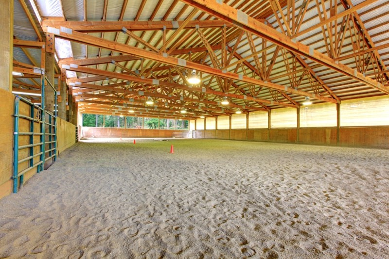 Large indoor horse arena with high wooden beams